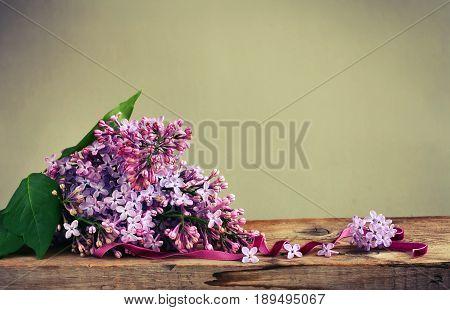 Bouquet fragrant violet lilac velvet ribbon on wooden table rustic vintage style