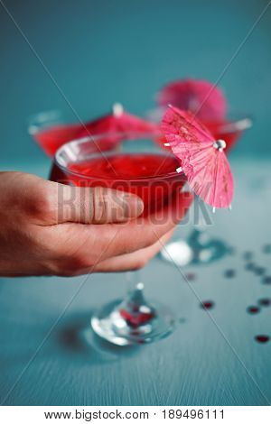 Raspberry cocktail with ice and paper umbrellas. Summer refreshing alcohol drinks for parties.