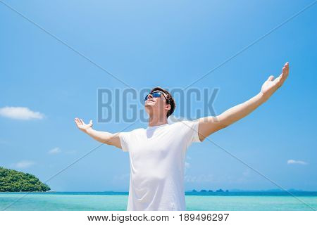 Young man raising his arms opening palms looking up in the air at the beach in summer - freedom and vacation concepts