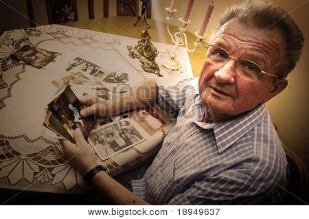 Senior man looking at old photographs. Reminisce about the past