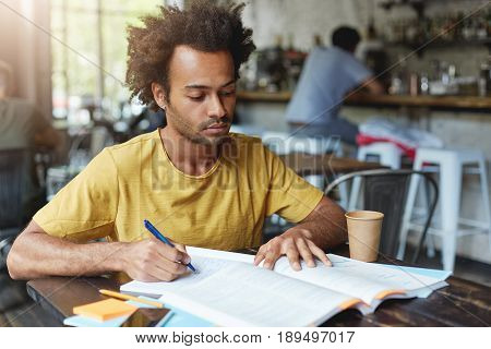 Concentrated Dark-skinned Male With African Hairstyle And Bristle Wearing Casual Clothes Writing Not