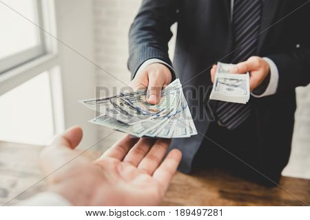 Businessman giving money US dollar bills - loanpayment bribery and corruption concepts