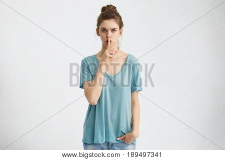 Secrecy, Privacy And Confidentiality. Attractive Young Woman With Serious Strict Look Holding Index