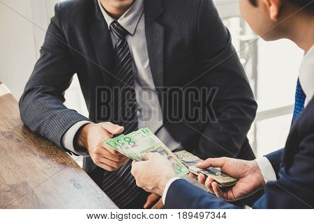 Businessman giving money Australian dollar bills to his partner - loan bribery and corruption concepts
