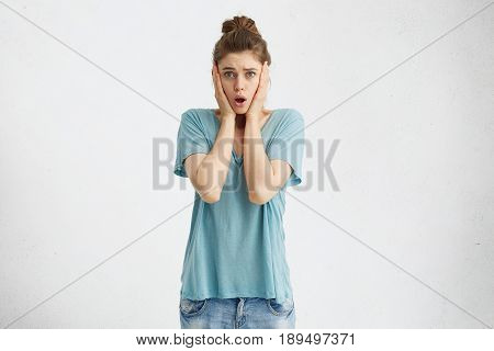 Oh No! Studio Shot Of Stressed Shocked Young European Woman With Hands On Her Cheeks And Mouth Dropp