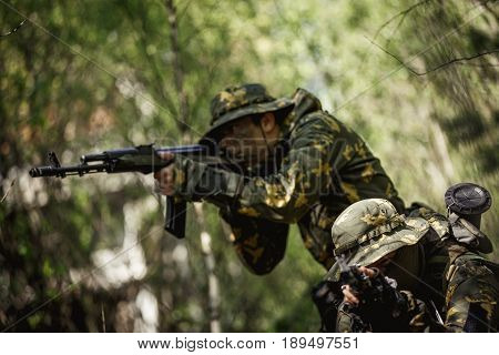 Portrait of military men with submachine gun in woods afternoon