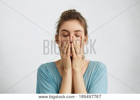 Headshot Of Young Beautiful Student Female Closing Her Eyes Holding Hands On Chin Being Tired After