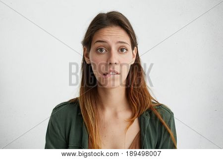 Horizontal Portrait Of Puzzled Woman With Long Face And Straight Dyed Hair Wearing Green Jacket Look