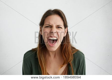 Close-up Of Irritated Woman Looking Angrily In Camera Shouting Having Wide Opened Mouth Being Annoye