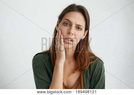 Horizontal Portrait Of Pretty Sad Woman With Bright Dark Eyes And Straight Hair Holding Hand On Chee