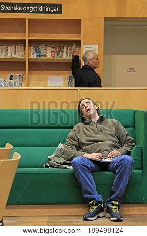 Man Is Sleeping On Sofa In Public Library