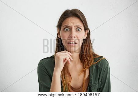 Shocked Dissatisfied Woman With Long Hair And Big Dark Eyes Wearing Casual Clothes Holding Hand On C