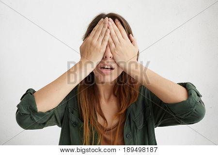 Isolated Studio Portrait Of Pretty Woman Covering Her Eyes With Hands. Young Desperate Woman Hiding