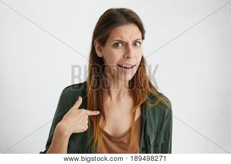 Portrait Of Beautiful Confused Woman Pointing At Herself With Index Finger. Offended Female Having Q