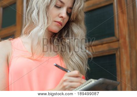 Beautiful young woman writes in a notebook. Photo on the street office style or student.