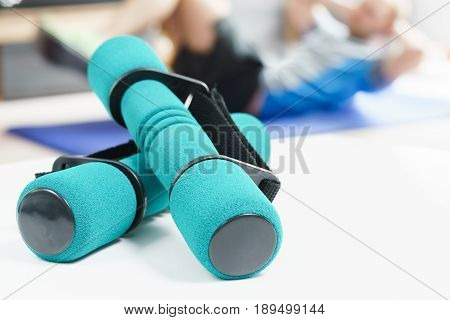 Fitness at home, green dumbbells in the foreground and man doing sit ups on exercise mat in the background in fitness in living room.