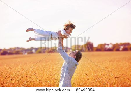 father lobbed her happy son who closed his eyes on the yellow wheat field among spikelets