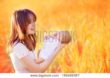 A newborn baby yawns in the arms of a mother standing in the middle of a yellow wheat field
