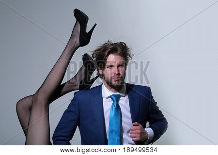handsome man or businessman in suit and female sexy legs in fashionable shoes and tights on grey background love and relations power boss office romance sexual services couple in love