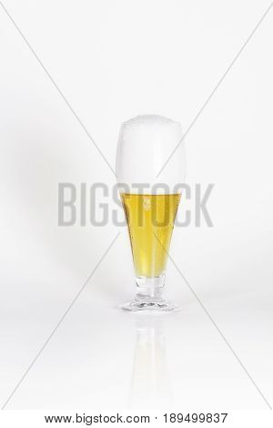 Glass of cold lager beer with foam on a white background isolated