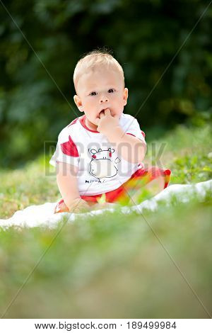 The kid in red shorts sits on a litter in the green grass thrusting his fingers in his mouth