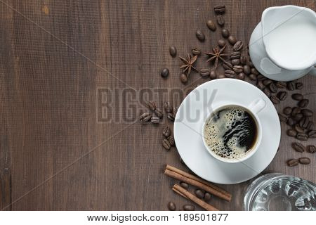 Cup of coffee cream in a milk jug glass of water and various spices on the wooden table with copy-space top view