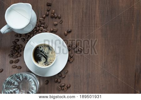 Cup of coffee cream in a milk jug glass of water and coffe beans on the wooden table with copy-space top view