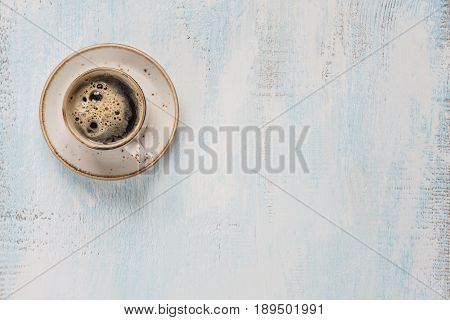 Black coffee with crema in vintage porcelain cup on a light wooden background with space for text top view