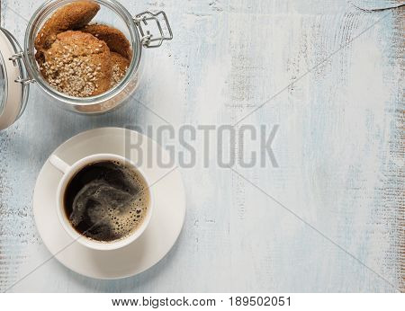 Black coffee with crema in white porcelain cup and oatmeal cookie in a glass jar on a light wooden background with space for text top view