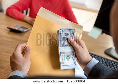 Businessman holding money behind the envelope at the office - bribery and corruption concepts