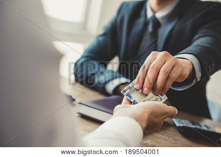 Businessman giving money US dollars to his partner in the office - loan bribery and corruption concepts