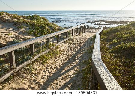 sandy walkway with wooden railings leading onto a tranquil beach at sunrise