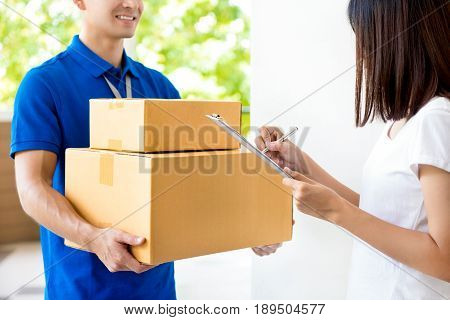 Woman signing document receiving parcel box from delivery man - courier service concept