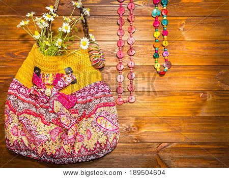 Bright Summer Accessories. Bag and Beads on wooden background