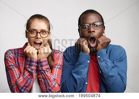 Terrified And Puzzled Couple With Opened Mouths Holding Fists Under Their Chins. Full Face Portrait