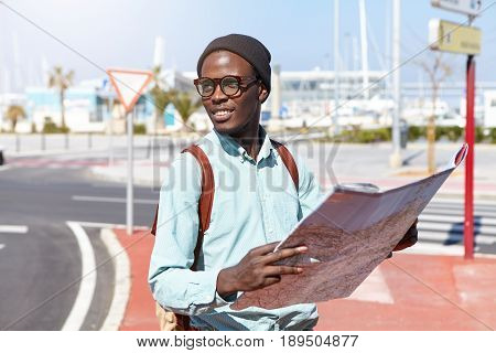 Potrait Of Dark-skinned Traveler In Trendy Black Hat, Eyeglasses And Shirt Holding Backpack And Map
