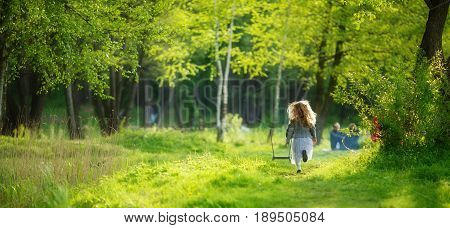 Girl runs along the grass in a park with green trees in the rays of the spring sun