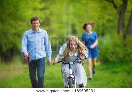 Family on a walk in the forest. A girl rushes on a bicycle on the green grass parents try to catch up with her on foot