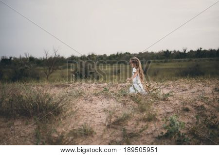 Blurred image Copy space Background Long-haired girl in white clothes Lonely runs Desert sand field near forest at sunset down. Selective focus. Toned image