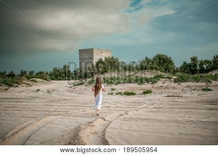 Blurred image Copy space Background Long-haired girl in white clothes Lonely runs Desert sand field to abandoned building near forest at sunset down. Selective focus. Toned image