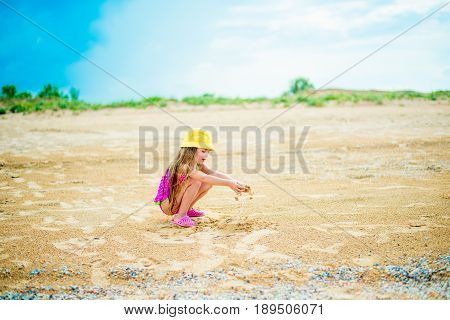 Little girl with long hair playing with sand on shore of beach sea on sunny day. Selective focus