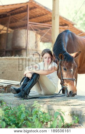 Young teenage girl equestrian sitting close to her chestnut horse. Vibrant multicolored summertime outdoors vertical image.
