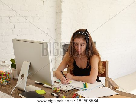 Portrait of mindful young female studying foreign languages on internet website making notes on stickers for better memorise new words. Copy space wall for advertising content or text.