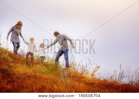 Family mom dad son and daughter go down the hill overgrown with a withered autumn tar. A man helps his children safely go downstairs