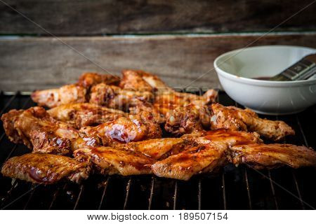 Preparing bbq hot chicken wings on grill