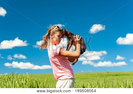 Young cheerful teenage girl in wheat field holding her lovely little toy-terrier dog. Multicolored vibrant outdoors summertime horizontal image with cloudy sky background.