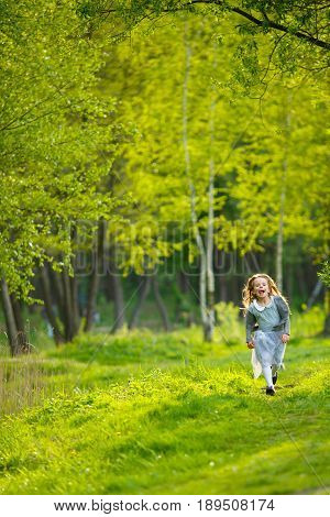 A little girl in a dress and with her tongue sticking out runs through the full-grown green grass in the forest