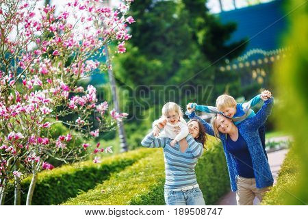 Same-sex lesbian family with two children on a walk in the park. Children have fun sitting on their mother's neck