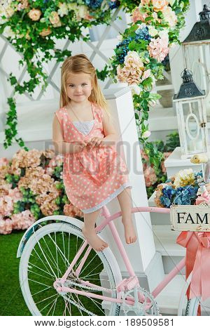 Little girl in pink dress with peas embarrassed sitting on pink bicycle background with floral wall