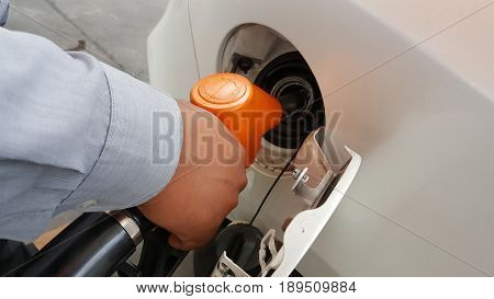 Hand refilling the car with fuel background
